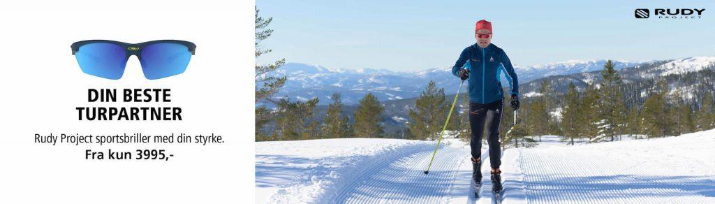 Mann med blå jakke går på ski mens han har på seg sportsbrillene Rudy Project Stratofly.