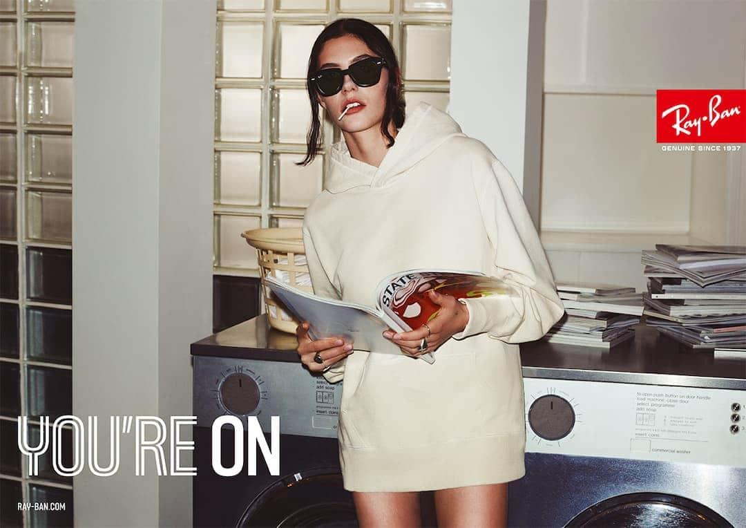 Dame med Ray-Ban solbriller som holder et magasin. Damen har på seg en stor hvit hettegenser og står foran en vaskemaskin og tørketrommel.